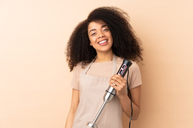 Young african american woman using hand blender isolated