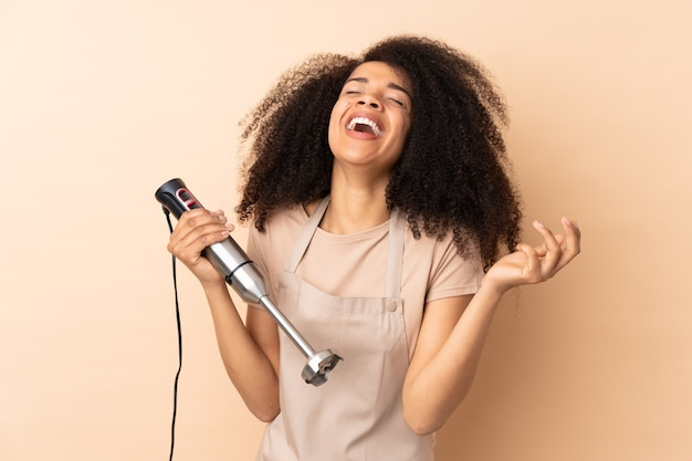 Young african american woman using hand blender laughing