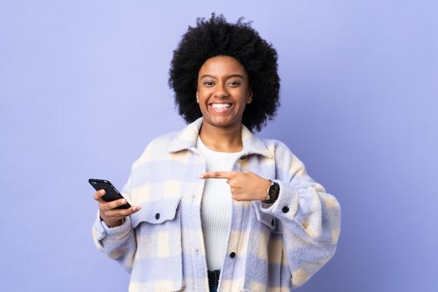 紫に分離され、それを指している携帯電話を使用して若いアフリカ系アメリカ人女性