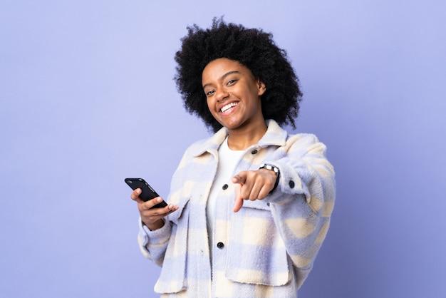 Молодая афроамериканская женщина с помощью мобильного телефона, изолированного на фиолетовом фоне, с уверенным выражением лица указывает пальцем на вас