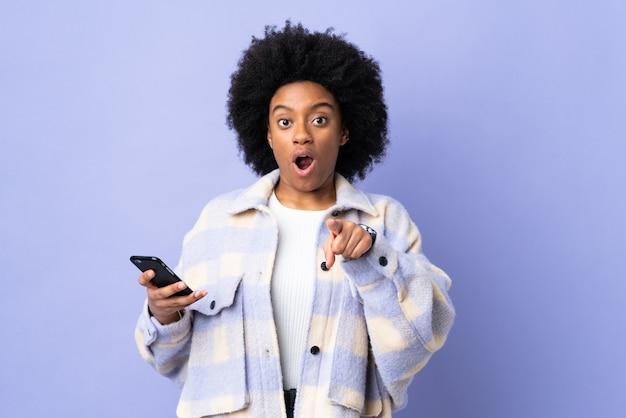 Молодая афро-американская женщина, использующая мобильный телефон, изолирована на фиолетовом фоне, удивлена и указывая вперед