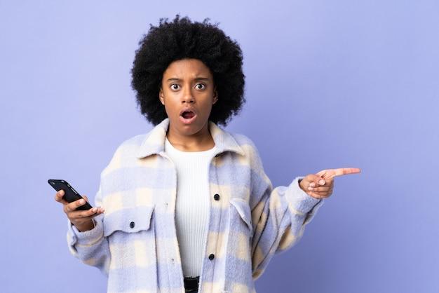 Молодая афро-американская женщина с помощью мобильного телефона, изолированного на фиолетовом фоне, удивлена и указывает сторону