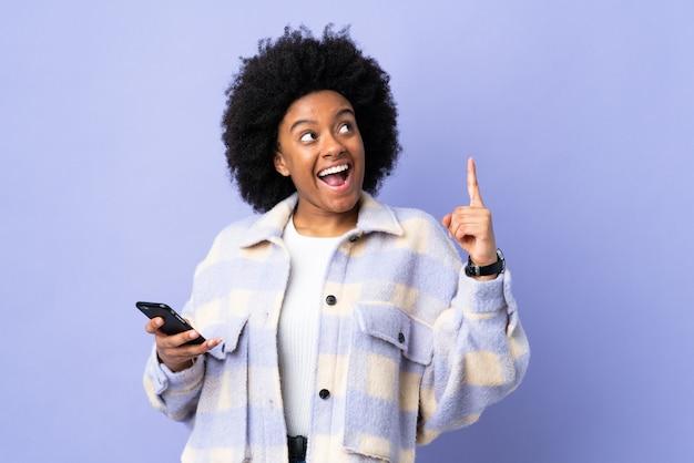 보라색에 고립 된 휴대 전화를 사용하는 젊은 아프리카 계 미국인 여자는 손가락을 들어 올리는 동안 솔루션을 실현하려는 의도