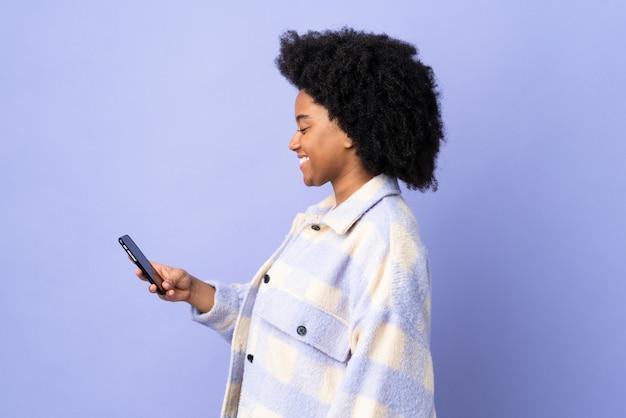 幸せな表情で紫に分離された携帯電話を使用して若いアフリカ系アメリカ人女性