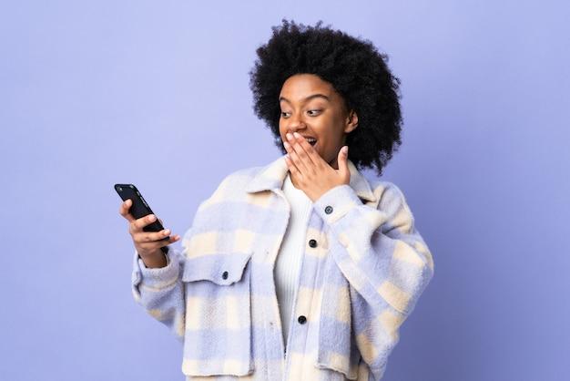 Молодая афроамериканская женщина, использующая мобильный телефон, изолирована на фиолетовом с удивленным и шокированным выражением лица