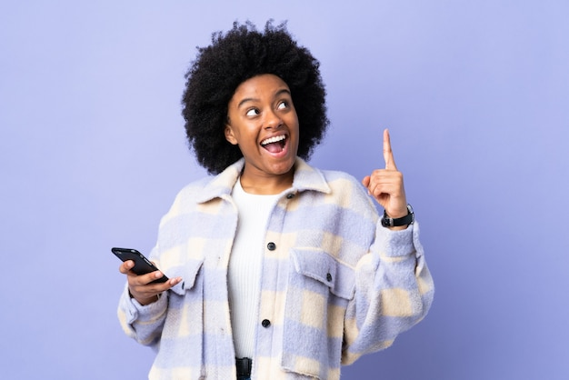 Young african american woman using mobile phone isolated on purple intending to realizes the solution while lifting a finger up