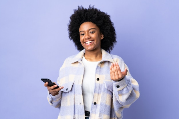 Young african american woman using mobile phone isolated on purple inviting to come with hand. happy that you came