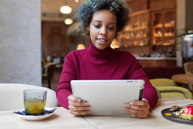 카페에서 태블릿 pc를 사용하는 젊은 아프리카계 미국인 여성