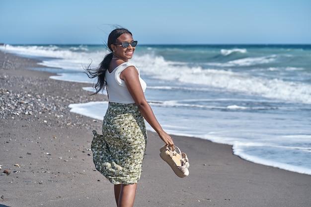 サンダルを手にビーチの海岸に沿って歩く若いアフリカ系アメリカ人の女性