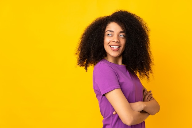 Young african american woman over wall with arms crossed and happy