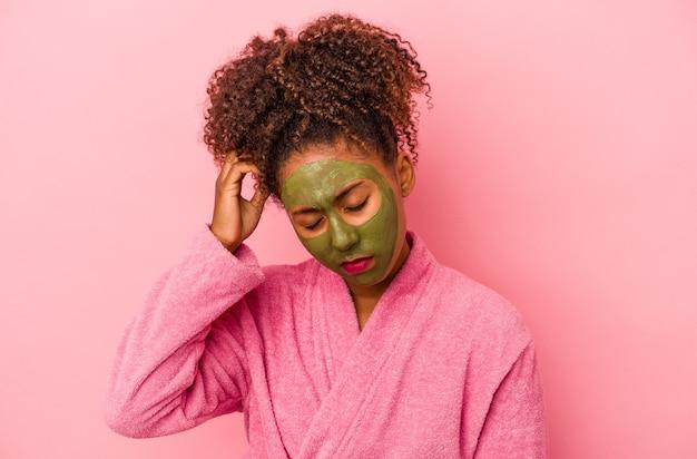 분홍색 배경에 격리된 목욕 가운과 얼굴 마스크를 쓴 젊은 아프리카계 미국인 여성은 충격을 받아 중요한 회의를 기억했습니다.