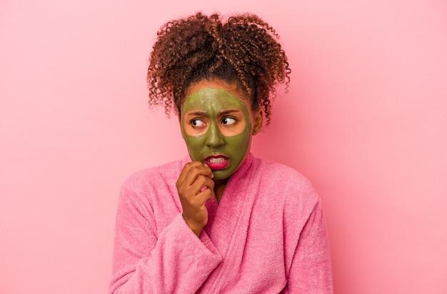 분홍색 배경에 격리된 목욕 가운과 얼굴 마스크를 쓴 젊은 아프리카 여성은 손톱을 물어뜯고 긴장하고 매우 불안해합니다.