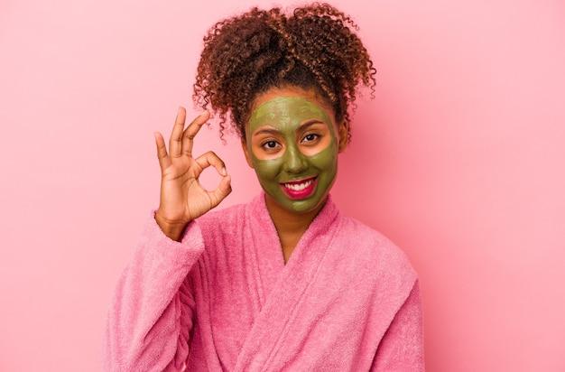 분홍색 배경에 격리된 목욕 가운과 안면 마스크를 쓴 젊은 아프리카계 미국인 여성은 쾌활하고 자신감 있는 제스처를 보여줍니다.