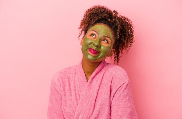 분홍색 배경에 격리된 목욕 가운과 얼굴 마스크를 쓴 젊은 아프리카계 미국인 여성은 목표와 목적을 달성하는 꿈을 꾸고 있습니다