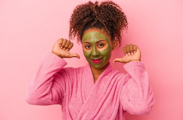 분홍색 배경에 격리된 목욕 가운과 안면 마스크를 쓴 젊은 아프리카계 미국인 여성은 자부심과 자신감을 느낍니다.