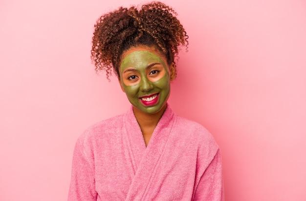 분홍색 배경에 격리된 목욕 가운과 안면 마스크를 쓴 젊은 아프리카계 미국인 여성은 행복하고 웃고 쾌활합니다.