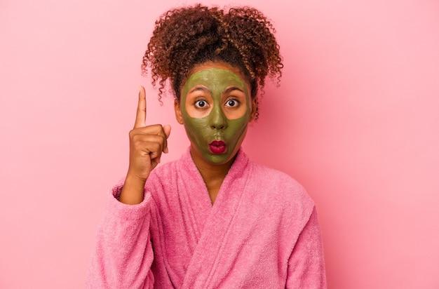 분홍색 배경에 격리된 목욕 가운과 얼굴 마스크를 쓴 젊은 아프리카계 미국인 여성은 훌륭한 아이디어, 창의성 개념을 가지고 있습니다.