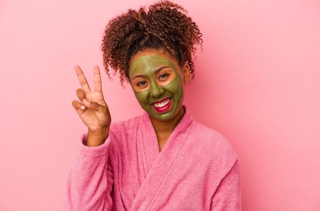 분홍색 배경에 격리된 목욕 가운과 얼굴 마스크를 쓴 젊은 아프리카계 미국인 여성은 손가락으로 평화의 상징을 보여주는 즐겁고 평온합니다.