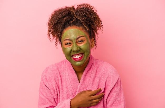 분홍색 배경에 격리된 목욕 가운과 안면 마스크를 쓴 젊은 아프리카계 미국인 여성이 웃고 즐겁게 지내고 있습니다.