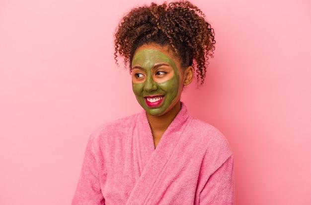 분홍색 배경에 격리된 목욕 가운과 안면 마스크를 쓴 젊은 아프리카계 미국인 여성은 옆으로 웃고, 명랑하고 유쾌해 보입니다.