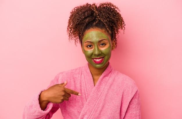 분홍색 배경에 격리된 목욕 가운과 얼굴 마스크를 쓴 젊은 아프리카계 미국인 여성이 셔츠 복사 공간을 손으로 가리키며 자랑스럽고 자신감이 넘칩니다