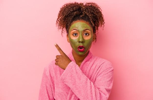 측면을 가리키는 분홍색 배경에 격리된 목욕 가운과 얼굴 마스크를 쓴 젊은 아프리카계 미국인 여성