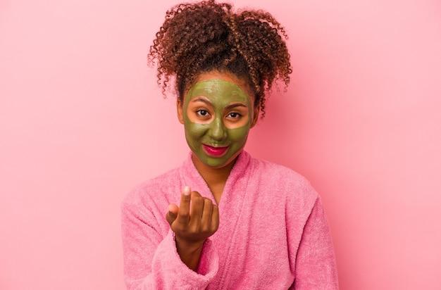 분홍색 배경에 격리된 목욕 가운과 얼굴 마스크를 쓴 젊은 아프리카계 미국인 여성이 마치 가까이 오는 것처럼 손가락으로 당신을 가리키고 있습니다.