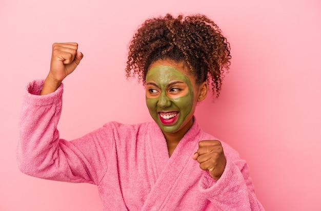분홍색 배경에 격리된 목욕 가운과 얼굴 마스크를 쓴 젊은 아프리카계 미국인 여성이 승리, 승자 개념으로 주먹을 들고 있습니다.