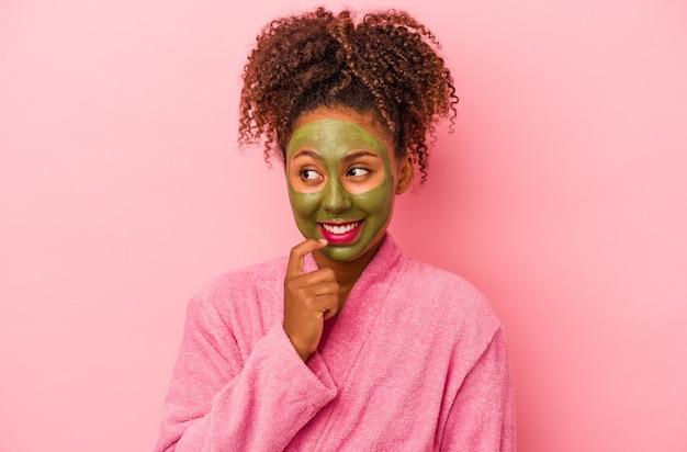 분홍색 배경에 격리된 목욕 가운과 안면 마스크를 쓴 젊은 아프리카계 미국인 여성은 복사 공간을 보고 있는 무언가에 대해 편안하게 생각했습니다.