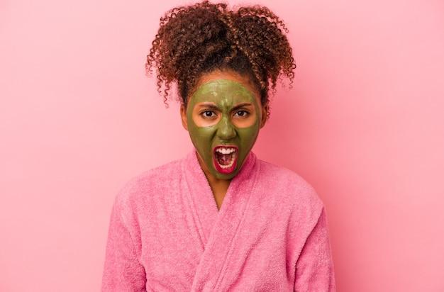 분홍색 배경에 격리된 목욕 가운과 얼굴 마스크를 쓴 젊은 아프리카계 미국인 여성이 매우 화를 내고 공격적으로 비명을 지르고 있습니다.