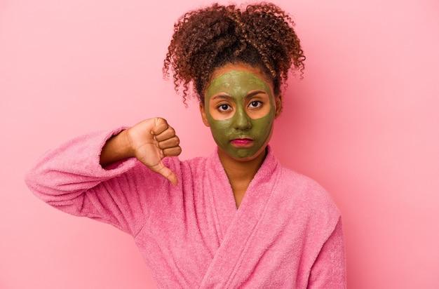 분홍색 배경에 격리된 목욕 가운과 안면 마스크를 쓴 젊은 아프리카계 미국인 여성이 싫어한다는 제스처를 보이고 엄지손가락을 아래로 내립니다. 불일치 개념입니다.