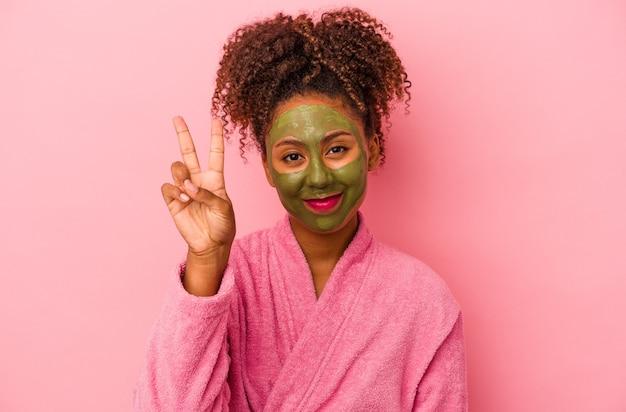 분홍색 배경에 격리된 목욕 가운과 얼굴 마스크를 쓴 젊은 아프리카계 미국인 여성이 손가락으로 2번을 보여줍니다.