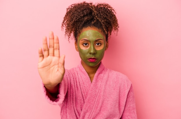 분홍색 배경에 격리된 목욕 가운과 안면 마스크를 쓴 젊은 아프리카계 미국인 여성이 정지 신호를 보여주는 뻗은 손으로 서서 당신을 막습니다.