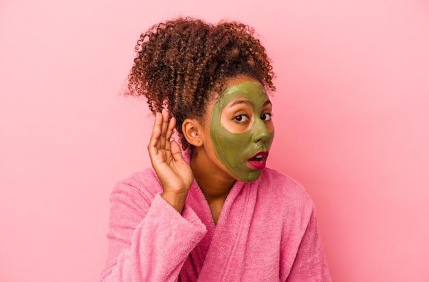 분홍색 배경에 격리된 목욕 가운과 얼굴 마스크를 쓴 젊은 아프리카계 미국인 여성이 가십을 들으려고 합니다.