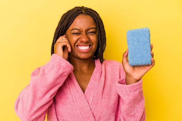 Молодая афро-американская женщина в халате, держащая синюю губку, изолированную на желтом фоне, прикрывая уши руками.