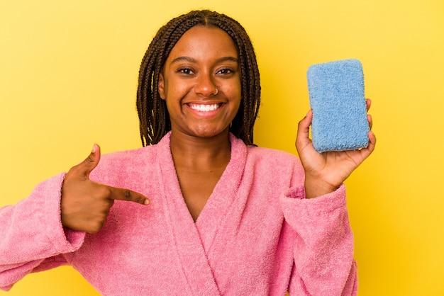 シャツのコピースペースを手で指している黄色の背景の人に分離された青いスポンジを保持しているバスローブを着ている若いアフリカ系アメリカ人女性、誇りと自信を持って