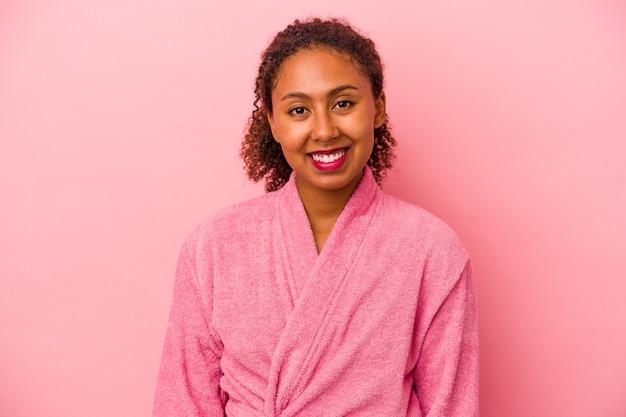 분홍색 배경에 격리된 목욕 가운을 입은 젊은 아프리카계 미국인 여성은 행복하고 웃고 쾌활합니다.