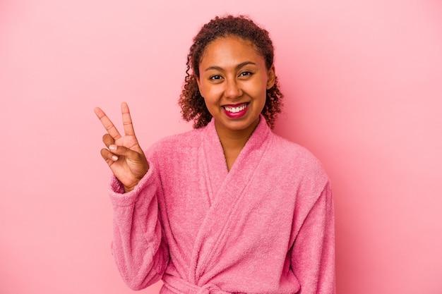 분홍색 배경에 격리된 목욕 가운을 입은 젊은 아프리카계 미국인 여성이 손가락으로 평화의 상징을 보여주는 즐겁고 평온합니다.