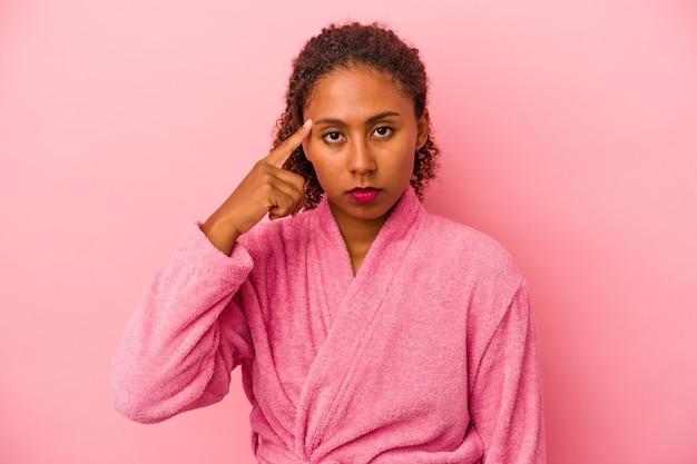 분홍색 배경에 격리된 목욕 가운을 입은 젊은 아프리카계 미국인 여성이 손가락으로 사원을 가리키며 생각하고 작업에 집중했습니다.