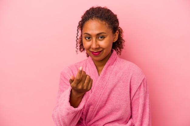분홍색 배경에 격리된 목욕 가운을 입은 젊은 아프리카계 미국인 여성이 마치 가까이 오는 것처럼 손가락으로 당신을 가리키고 있습니다.