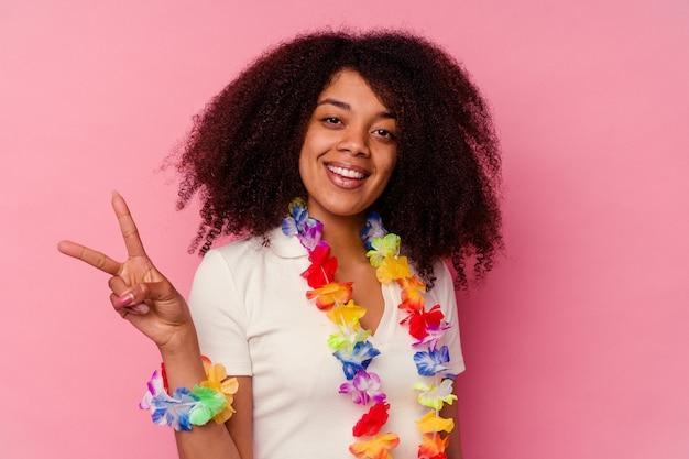 ハワイアンのものを身に着けている若いアフリカ系アメリカ人女性は、指で平和のシンボルを示して楽しくてのんきです。