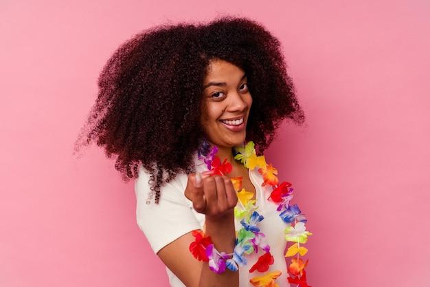 ハワイアンのものを身に着けている若いアフリカ系アメリカ人の女性が、誘うようにあなたに指を向けています。