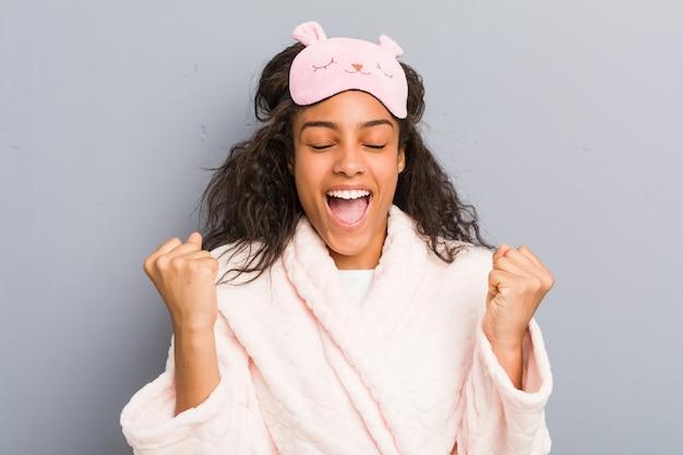 パジャマと睡眠マスクを身に着けている若いアフリカ系アメリカ人女性は、のんきで興奮を応援します。勝利のコンセプト。