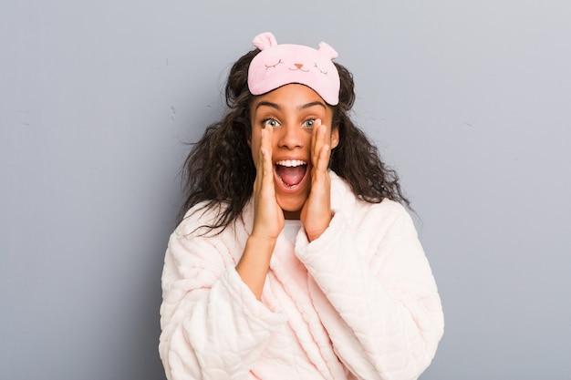 パジャマと睡眠マスクを着た若いアフリカ系アメリカ人女性が前に興奮していた。