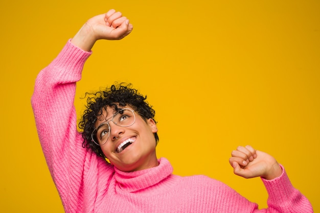 Молодая афро-американская женщина нося розовый свитер празднуя особый день, скачки и поднимает оружия с энергией.