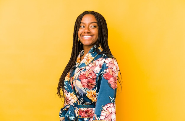 Young african american woman wearing an asiatic pijama isolated looks aside smiling, cheerful and pleasant.