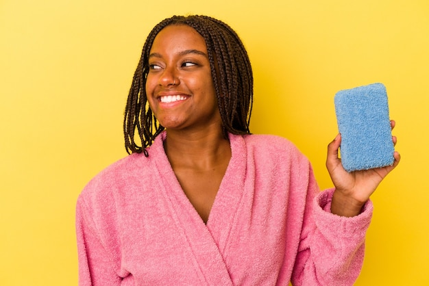 Young african american woman wearing a bathrobe holding a blue sponge isolated on yellow background  looks aside smiling, cheerful and pleasant.