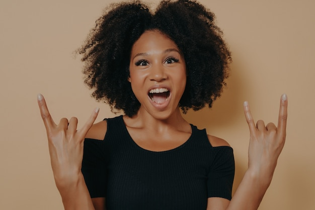 Young african american woman wearing black tshirt shouting with crazy facial expression doing rock-n-roll symbol with hands up like music star, isolated over beige studio background with copy space