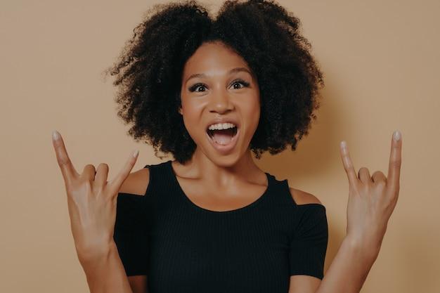 Молодая афро-американская женщина в черной футболке кричит с сумасшедшим выражением лица и делает символ рок-н-ролла с поднятыми руками, как музыкальная звезда, изолированная на бежевом студийном фоне с копией пространства