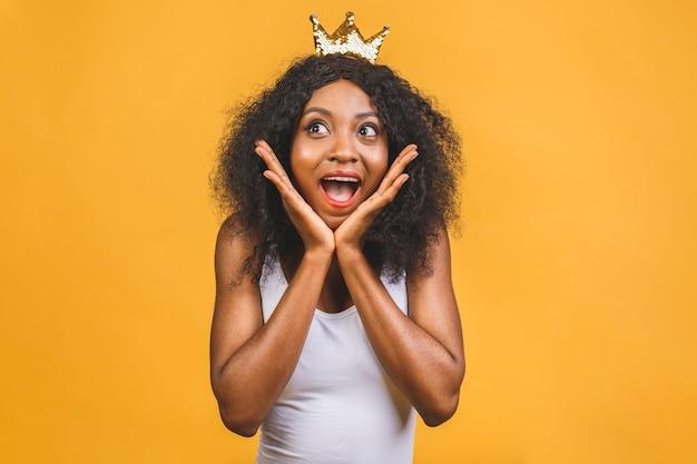 顔に幸せでクールな笑顔で女王の黄金の冠を着ている若いアフリカ系アメリカ人女性
